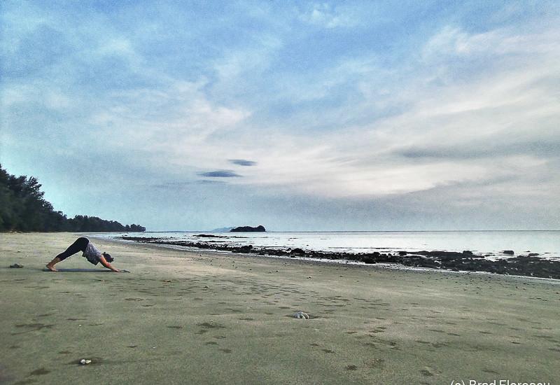 Laura face yoga pe plaja pustie.